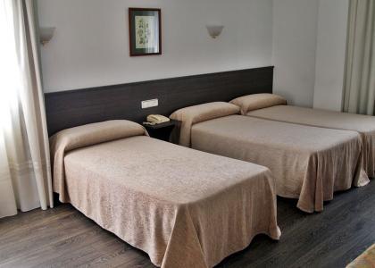 Ámplia habitación con tres camas individuales